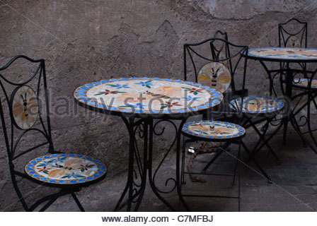Blue Wrought Iron Table And Chairs On A Patio Covered With
