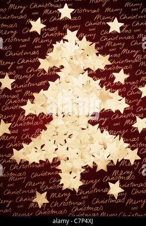 Christmas tree made from star shaped confetti on a fabric background - Stock Photo