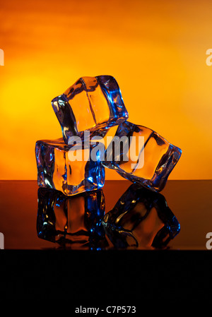 'Fire and Ice' Ice cubes melting in front of  a warm background - Stock Photo