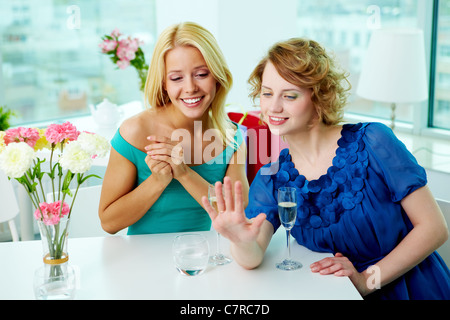 Young woman showing wedding ring to her girlfriend in cafe - Stock Photo