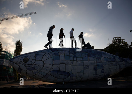 local children playing on 'The Big Fish' Salmon sculpture by John Kindness next to the River Lagan in Belfast City - Stock Photo