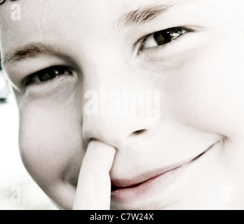 Close-up of a boy picking his nose - Stockfoto