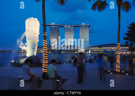 The Merlion statue and Marina Bay Sands Hotel at dusk, Singapore - Stock Photo
