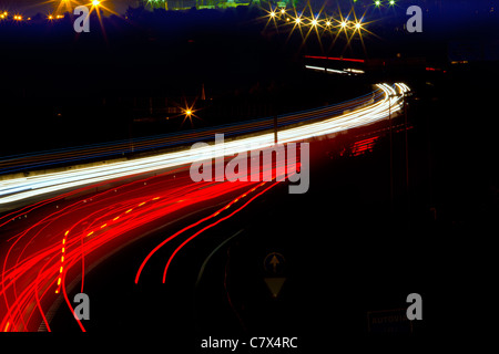 car light trails in red and white on night road curve - Stockfoto