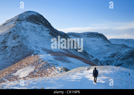 Walker approaching Cat Bells in winter. Lake District National Park. Cumbria, England, UK. - Stock Photo