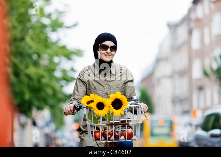 Woman in headscarf biking on cell phone - Stock Photo