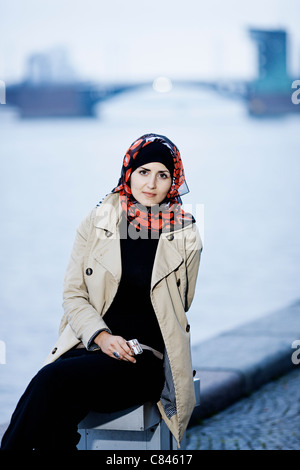 Woman in headscarf sitting on bench - Stock Photo