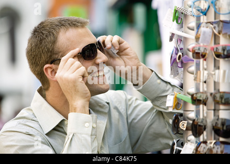 Man trying on sunglasses in street market - Stock Photo