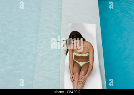Young woman sitting on deckchair by pool - Stockfoto