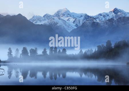 Reflection of Mt Cook (Aoraki) and Mt Tasman on Lake Matheson near Fox Glacier in New Zealand - Stock Photo