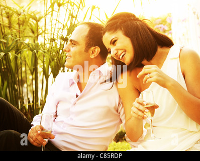Happy young couple drinking champagne outdoor, laughing and enjoying wedding day - Stock Photo