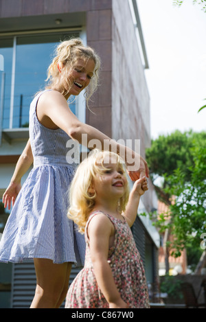 Mother and young daughter walking hand-in-hand outdoors - Stock Photo