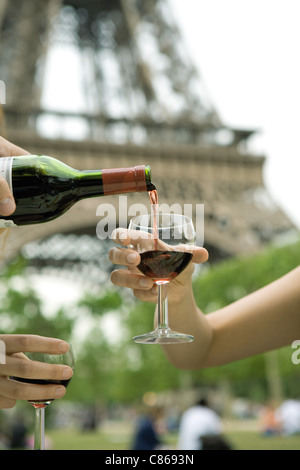 Pouring glass of red wine outdoors - Stock Photo