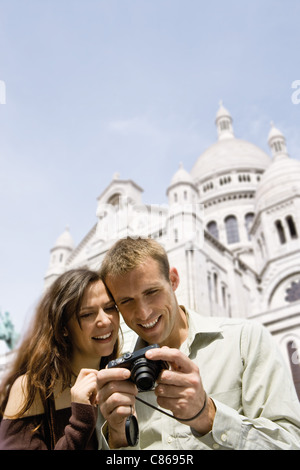 Sightseeing couple looking at digital camera, Sacre Coeur, Montmartre, Paris, France - Stock Photo