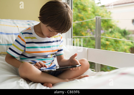 Boy sitting on bed, using digital tablet - Stock Photo