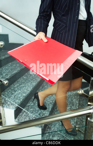 Close-up of businesswoman with red folder going down the stairs - Stock Photo