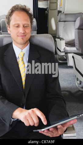 Germany, Bavaria, Munich, Businessman using Tablet PC in business class airplane cabin, smiling - Stock Photo