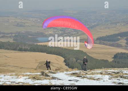 Hand gliding from Holme Moss on a cold winters day,with views of Holme valley in the distance. - Stock Photo