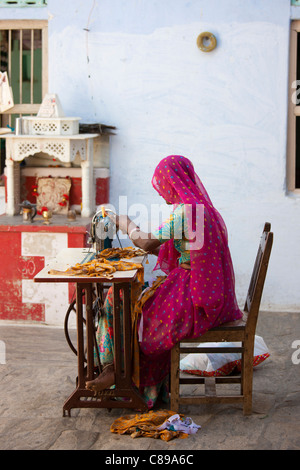 Indian woman in Rajasthani sari works at home using sewing machine in Nimaj village, Rajasthan, India - Stock Photo