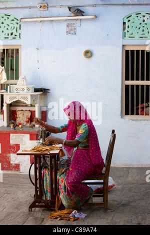 Indian homeworker woman in traditional Rajasthani sari works sewing machine in village of Nimaj, Rajasthan, India - Stock Photo