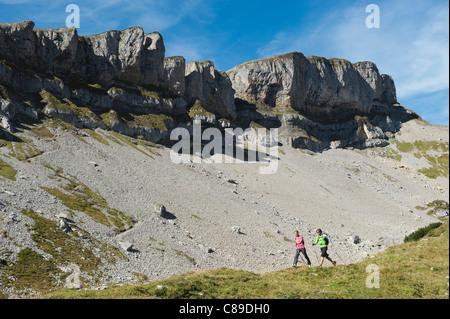 Austria, Kleinwalsertal, Man and woman hiking on mountain trail - Stock Photo