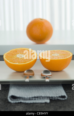 Half cut oranges with spoons, close up - Stock Photo