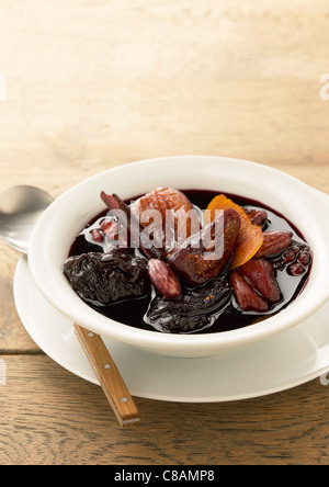 Dried fruit stewed in red wine with cinnamon - Stock Photo