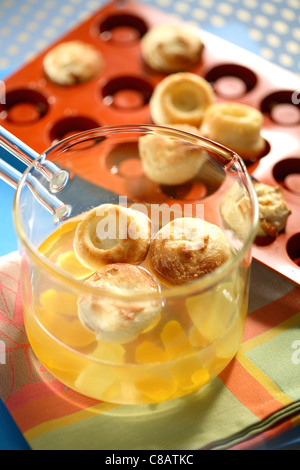 Soaking the Babas Bouchons in the citrus fruit and honey syrup - Stock Photo