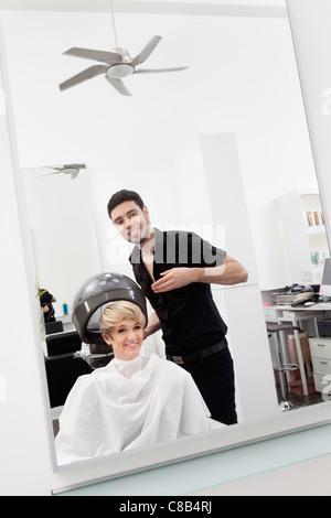 Woman under hair dryer at beauty salon - Stock Photo
