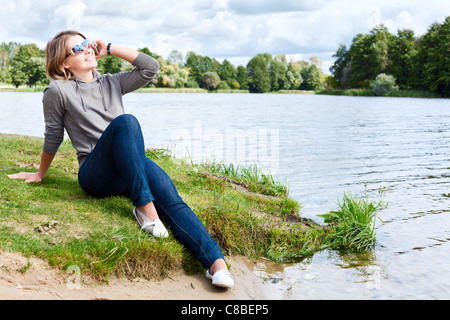 Young woman with sunglasses sitting on the shore of river and talking on the cellphone. Summer sunny day - Stockfoto