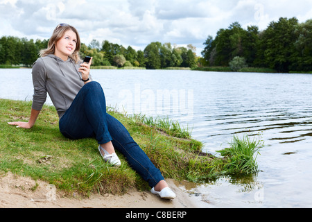 Young woman with sunglasses sitting on the shore of river and reading a message on the cellphone. Summer sunny day - Stockfoto
