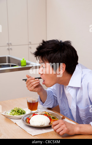 Mid adult man eating pepper steak - Stockfoto