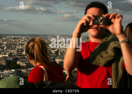 Tourists take pictures of the panorama of Paris from the Eiffel Tower in Paris, France. - Stock Photo