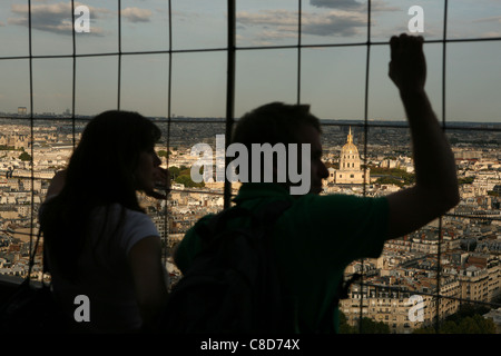 Tourists observe the panorama of Paris with the Chapel of Saint-Louis-des-Invalides from the Eiffel Tower in Paris, - Stock Photo