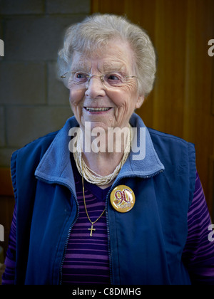 Healthy and smiling 90 year old lady on her birthday and wearing an appropriate lapel badge. England UK Europe - Stock Photo