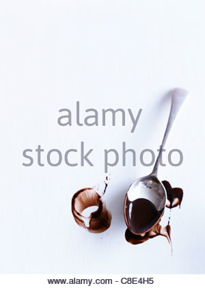 Spoon dipped in melted chocolate and marks of chocolate - Stock Photo