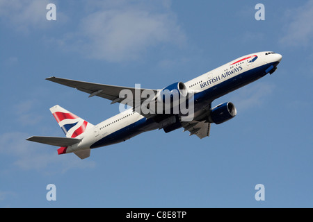 British Airways Boeing 777-200ER climbing on departure against a blue sky - Stock Photo
