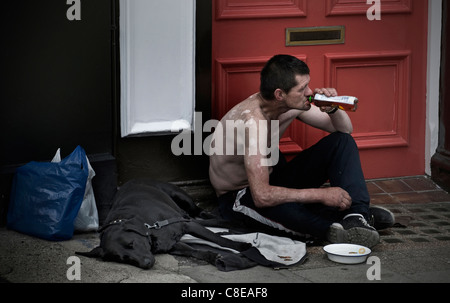 Homeless man with his dog sitting with begging bowl on shopping center high street drinking spirit alcohol ignored - Stock Photo
