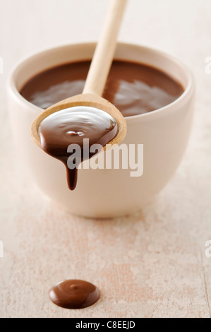 Bowl and spoonful of melted chocolate - Stock Photo