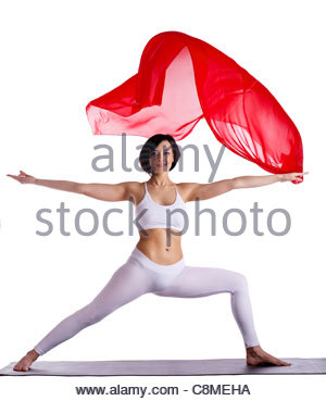 Young beauty woman exercise yoga pose and red flying cloth on mat - Stock Photo