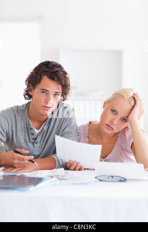 Unhappy couple reading a letter - Stock Photo