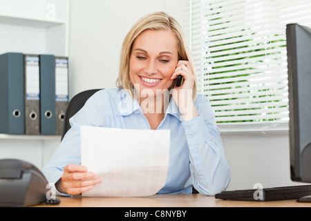 Portrait of a businesswoman reading a letter while phoning - Stock Photo