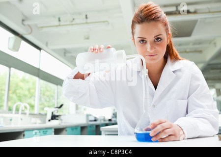 Red-haired scientist pouring liquid in a flask - Stock Photo