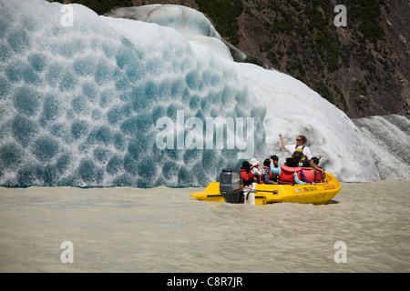 Tourists get close to an iceberg in the Tasman Glacier Terminal Lake, New Zealand - Stock Photo