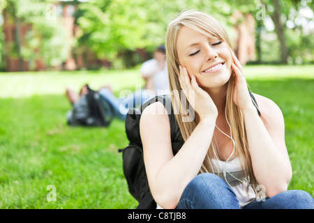 USA, Washington, Seattle, Woman listening to mp3 player in park - Stock Photo