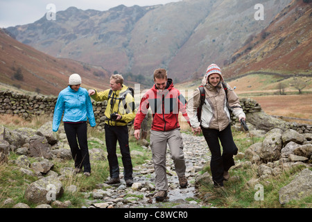 Four young millennial people walking enjoying a walk in Langstrath Valley in mountains of Lake District National - Stock Photo