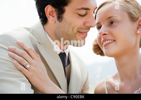 Bride wearing wedding ring with hand on groom's shoulder - Stock Photo
