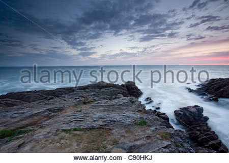 Rocks jutting into ocean under sky - Stock Photo