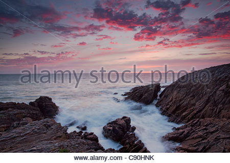 Rocks jutting into ocean under dramatic sky - Stock Photo