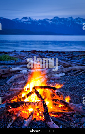 Campfire at dusk on a remote coastal beach in Goose Cove, Muir Inlet, Glacier Bay National Park, Alaska - Stock Photo